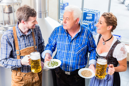 checking ingredients: Brewer and couple in beer brewery guided tour