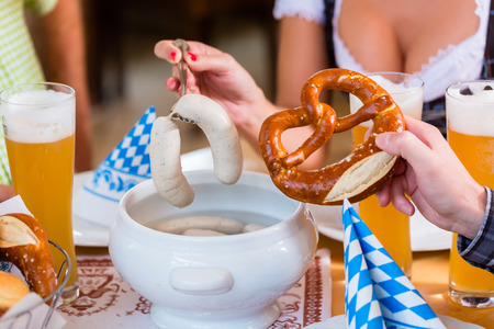 veal sausage: People eating veal sausage in bavarian restaurant Stock Photo