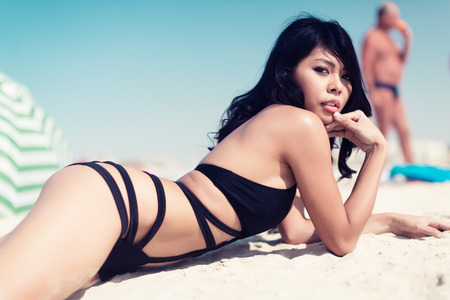 sexy asian woman: Sexy Asian woman on beach vacation lying in water wearing swimwear