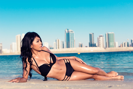 young girl bikini: Sexy woman lying on Al Mamzar city beach, Dubai, close to the water