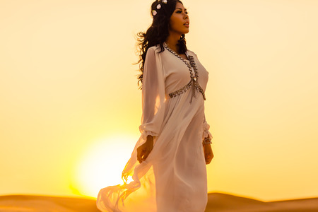 Beautiful girl standing in desert sunset photo