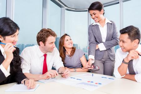 ganancias: equipo de negocios con miembros asi�ticos y cauc�sicos discutir ganancias con gr�ficos financieros sobre la mesa Foto de archivo