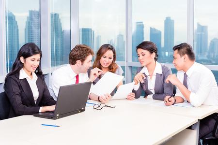 Asian Business Team in Strategie-Meeting im Büro mit Skyline der Stadt im Hintergrund