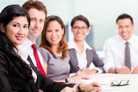 diversidad: Asia Equipo de negocios en reuni�n de la conferencia que mira la c�mara