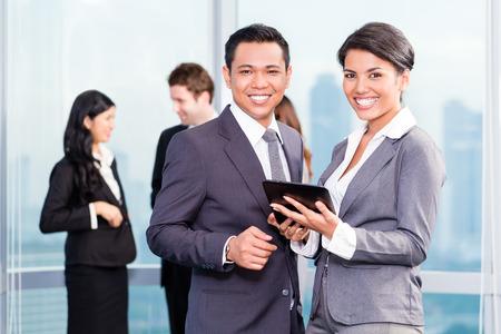 business asia: Asian business team di fronte skyline urbano presentazione discutere