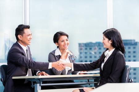 Asian recruitment team hiring candidate in job interview Foto de archivo