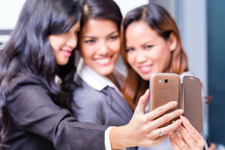 group picture: Asian Business women taking selfie with smart phone Stock Photo
