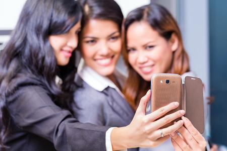 asian business women: Asian Business women taking selfie with smart phone Stock Photo