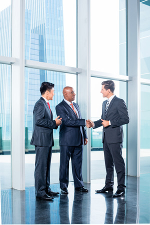 saludo de manos: Equipo de negocios Diversidad concluir contrato con apret�n de manos delante de horizonte de la ciudad