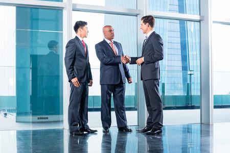 contrato de trabajo: Equipo de negocios Diversidad concluir contrato con apretón de manos delante de horizonte de la ciudad