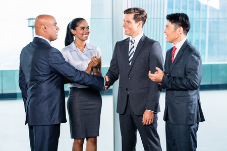 concluding: Diversity business team concluding contract with handshake in front of city skyline