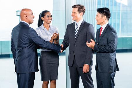 Equipo de negocios Diversidad concluir contrato con apretón de manos delante de horizonte de la ciudad