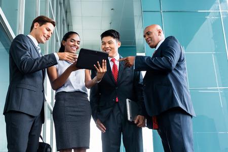 business asia: Pan asiatica e caucasica business team guardando computer tablet guardando presentazione del nuovo progetto