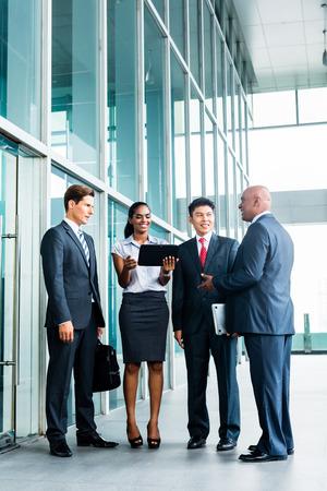 profesionistas: Pan equipo de negocios asi�ticos y cauc�sicos mirando la computadora tablet viendo la presentaci�n de nuevos proyectos
