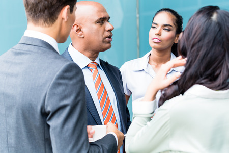 business asia: Business team con persone indiane, caucasici e indonesiani avendo caff� davanti skyline della citt� Archivio Fotografico