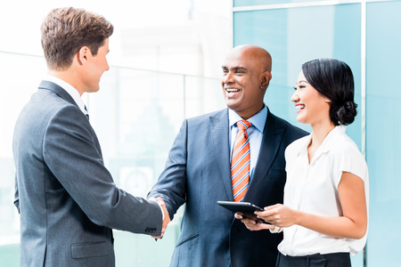 shake hand: Indian CEO and Caucasian executive having business handshake in front of city skyline Stock Photo