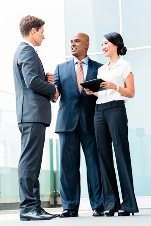 Indian CEO and Caucasian executive having business handshake in front of city skyline Stock Photo