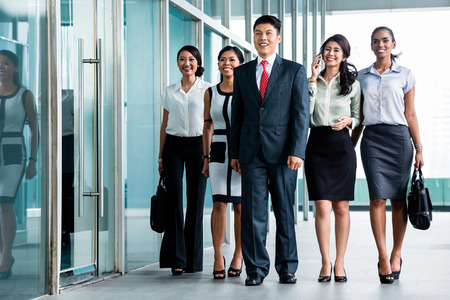 Asian business team of executives walking into office very determined to find some fault in the books they will do revision in