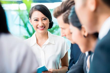 中国の女性は、カメラに探しているビジネスミーティング チーム アジアおよびコーカサス地方エグゼクティブ 写真素材