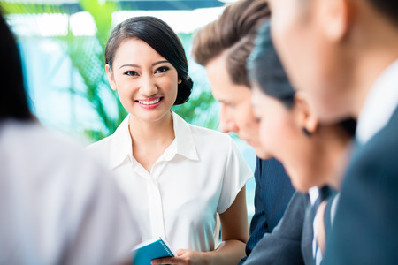 looking into: Business team meeting of Asian and Caucasian executives, Chinese woman is looking into the camera Stock Photo