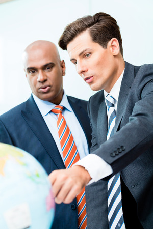 offshoring: Indian and Caucasian business men discussing offshoring project looking at globe exploring new markets Stock Photo
