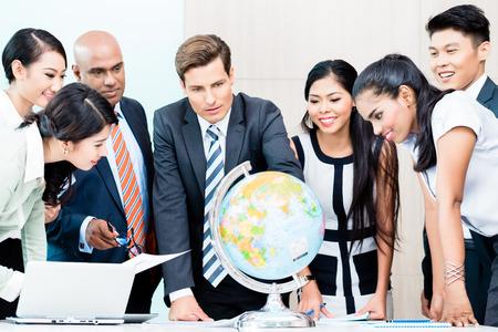 globe terrestre: Business team discuter renseignements disponibles sur le march� pour l'externalisation de plans regardant monde, les gens, caucasien, chinois et indon�siens indiennes