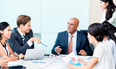 diversidad: Personas de la diversidad en la reunión de desarrollo de negocios con gráficos, CEO de la India y los números de crujido ejecutivos de raza blanca, cuadros y figuras en el escritorio