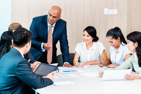 Diversity-Team in der Geschäftsentwicklung Treffen mit Charts, Indian und kaukasischen CEO Executive Knirschen Zahlen, Diagramme und Zahlen auf den Tisch