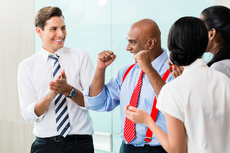 business asia: Business team celebrating success applauding and shaking fists Stock Photo