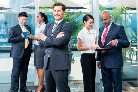 Business executive in front of his team of mixed ethnicities, Caucasian, Indian, Chinese, and Indonesian photo