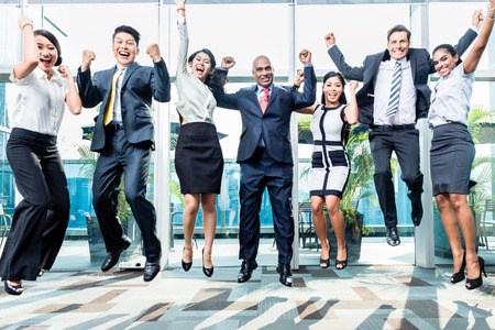 Diversity business team jumping celebrating success, Chinese, Indonesian, Indian, and Caucasian ethnicities Stockfoto