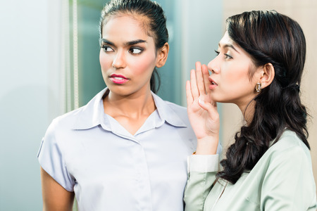 Gossip in the office, one woman whispering in ear of second business executive