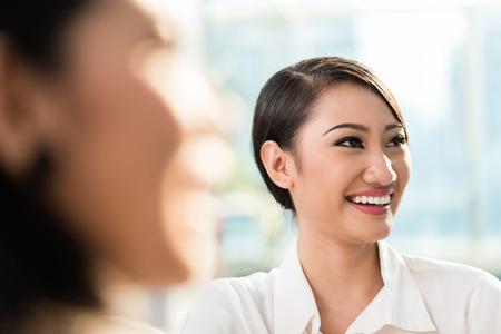 mujeres trabajando: Mujer de negocios chino en la reuni�n del equipo