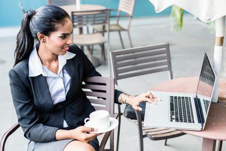 Indian Business Frau arbeitet mit Laptop sitzen auf der Terrasse vor der Skyline der Stadt