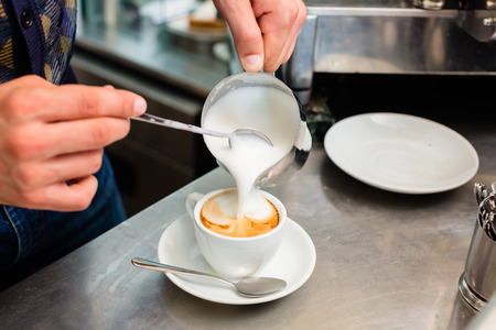 barista: Barista in cafe or coffee bar preparing proper cappuccino pouring milk froth in a cup