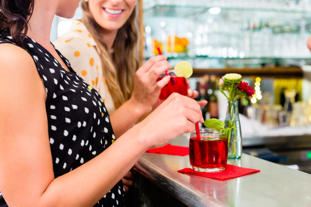 Two women friends in cafe bar drinking long drink or cocktails