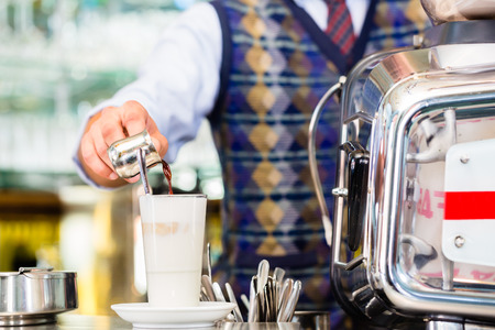 macchiato: Barista in cafe or coffee bar preparing pouring espresso shot in glass of latte macchiato