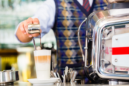 with coffee maker: Barista in cafe or coffee bar preparing pouring espresso shot in glass of latte macchiato