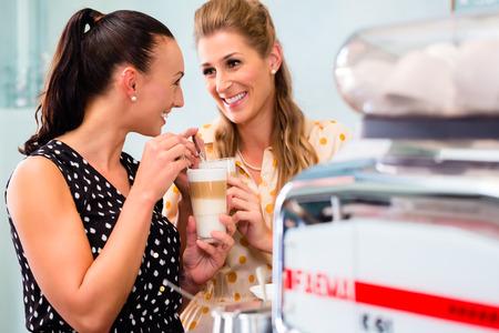 latte macchiato: Two girls, best friends, drinking latte macchiato in cafe or coffee bar
