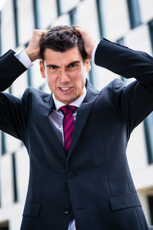 blunder: Angry business man tearing his hair in despair Stock Photo