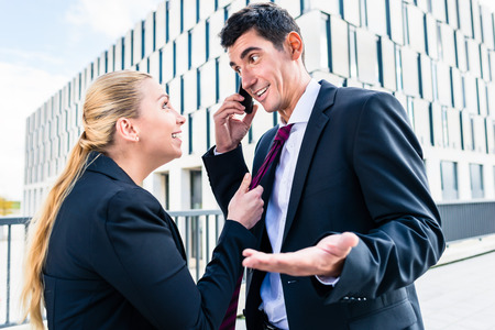 teasing: Flirt in the workplace - woman teasing man who is trying to work