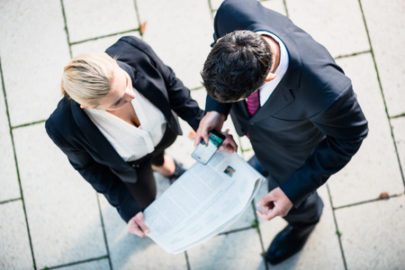 woman tie: Business man and woman  with newspaper and smart phone standing on square, seen in top view