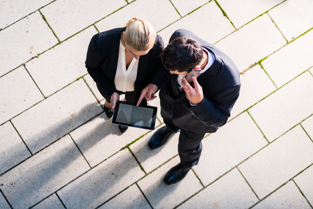 Business man and woman  with tablet computer standing on square, seen in top view photo