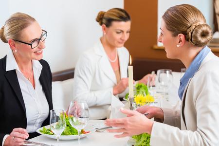 almuerzo: Reuni�n Empresarias en la cena de negocios o almuerzo en restaurante Foto de archivo