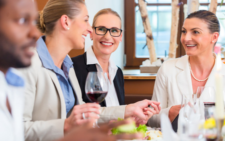 women working: Group of men and women at business lunch in restaurant eating and drinking