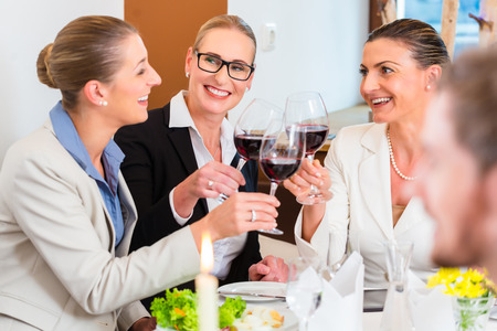 Group of men and women at business lunch in restaurant eating and drinking photo