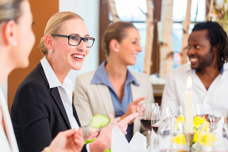 lunch meeting: Group of men and women at business lunch in restaurant eating and drinking