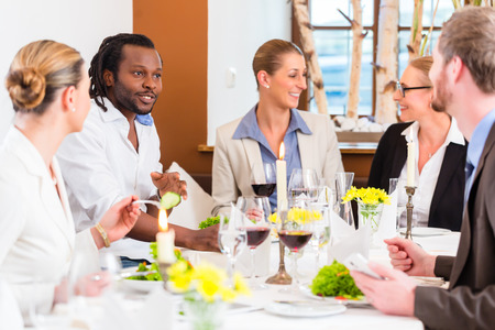 business dinner: Group of men and women at business lunch in restaurant eating and drinking