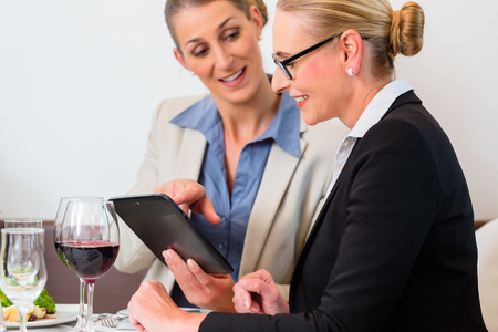 business dinner: Two business women discussing presentation in restaurant having lunch Stock Photo