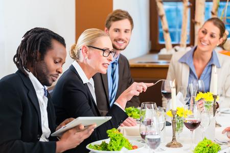 Équipe lors de la réunion de déjeuner d'affaires au restaurant manger et de boire dans la célébration de bon travail ensemble, de la nourriture et des boissons sur la table en arrière-plan